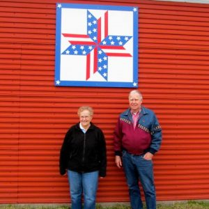 Gary and Rita Stracek with Stars and Stripes Forever barn quilt